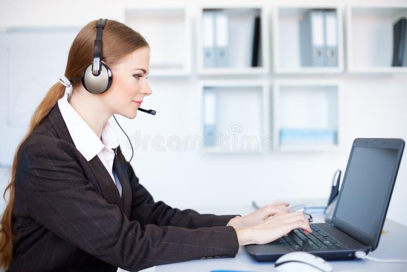 Weiblicher Bediener, der am Büroschreibtisch mit headse sitzt lizenzfreies stockbild