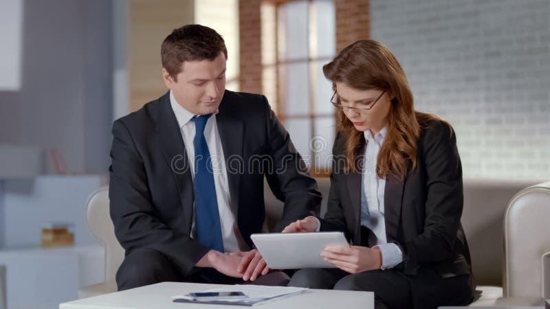 Weiblicher behilflicher Diskussionsunternehmensplan mit CEO, Projekt auf Tablette zeigend lizenzfreies stockfoto