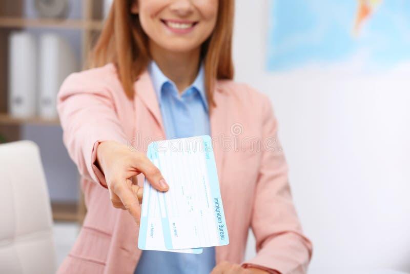 Weiblicher Berater, der Karten im Reisebüro hält stockfoto