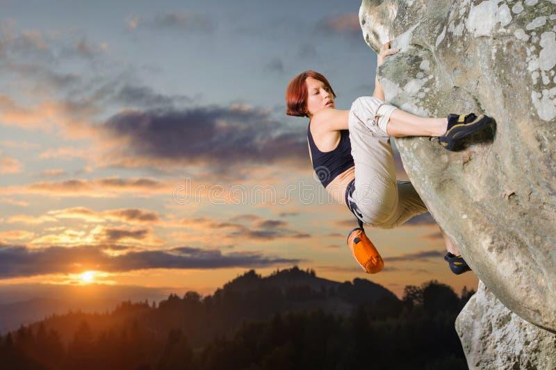 Weiblicher Bergsteiger, der ohne Seil auf einer felsigen Wand klettert lizenzfreies stockbild