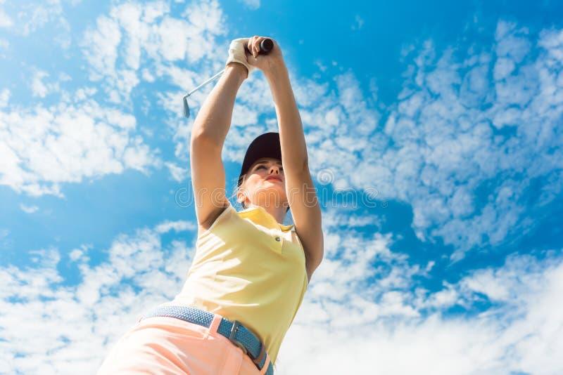 Weiblicher Berufsspieler, der den Eisenclub beim Spielen des Golfs hält stockfotografie