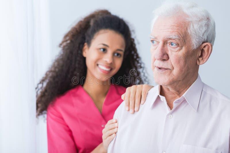 Weiblicher Betreuer, der älteren Mann unterstützt stockfotos