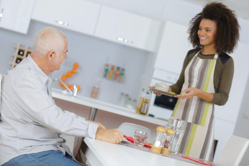 Weiblicher Betreuer, der älteren Mann unterstützt und stützt lizenzfreies stockfoto