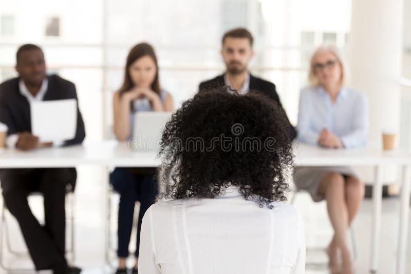 Weiblicher Bewerber des Afroamerikaners an der hinteren Ansicht des Vorstellungsgesprächs lizenzfreies stockbild