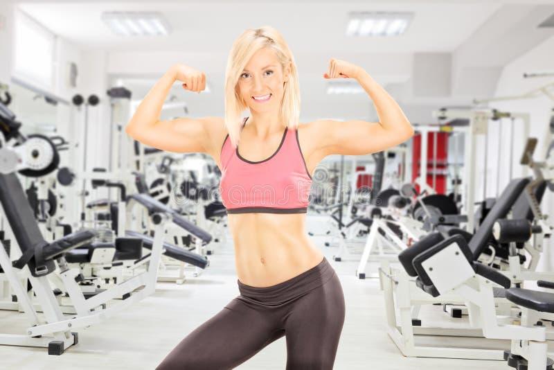 Weiblicher Bodybuilder, der ihr Bizeps in einer Turnhalle zeigt lizenzfreies stockfoto