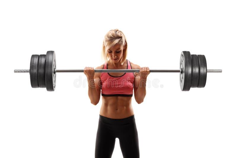 Weiblicher Bodybuilder, der mit einem Barbell trainiert lizenzfreie stockfotografie