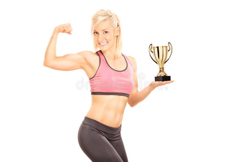 Weiblicher Bodybuilder, der Schale hält und Bizeps zeigt stockbilder