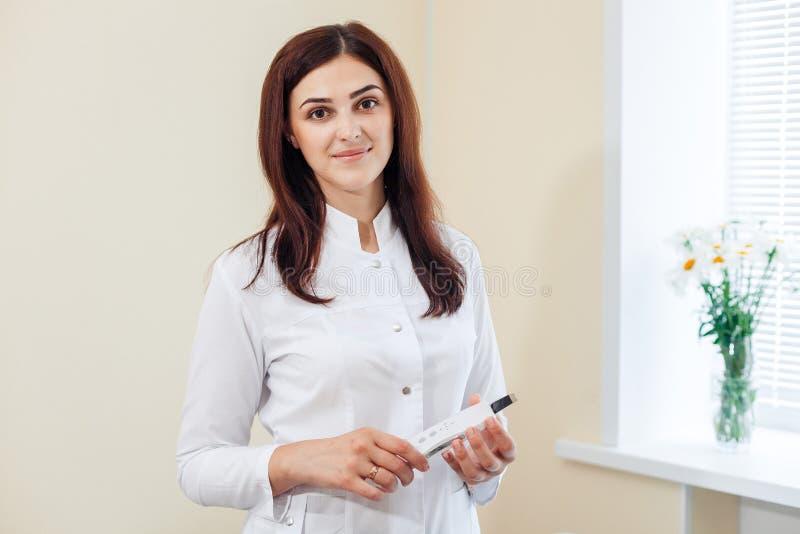 Weiblicher Brunette Cosmetologist in der Uniform nahe dem Fenster, welches das Ultraschall-scraber im Cosmetologybüro hält lizenzfreies stockbild
