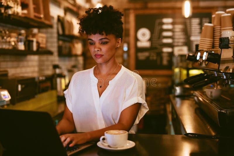 Weiblicher Caf?inhaber unter Verwendung des Laptops lizenzfreie stockfotos