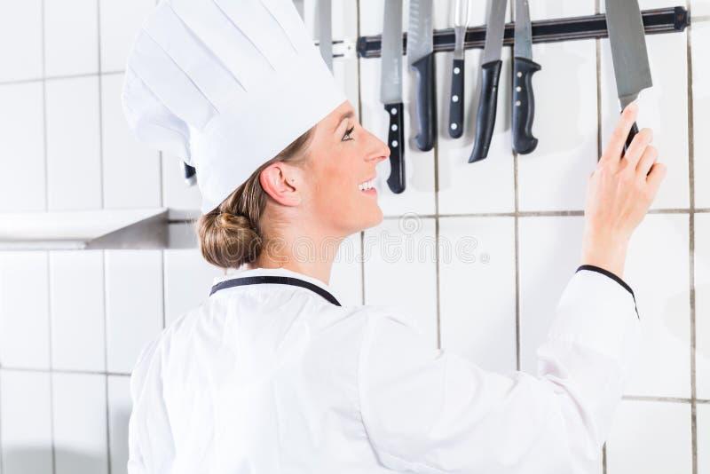 Weiblicher Chef in der industriellen Küche, die Messer von der Wandklammer nimmt lizenzfreies stockbild