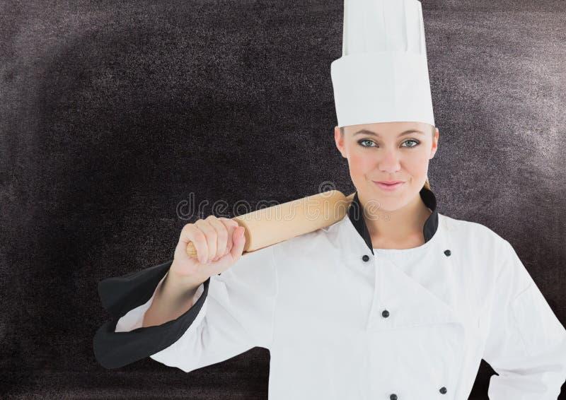 Weiblicher Chef, der Nudelholz gegen schwarzen Hintergrund hält stockbilder