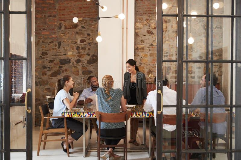 Weiblicher Chef, der zu Geschäftsteam in einem Konferenzzimmer spricht lizenzfreies stockfoto