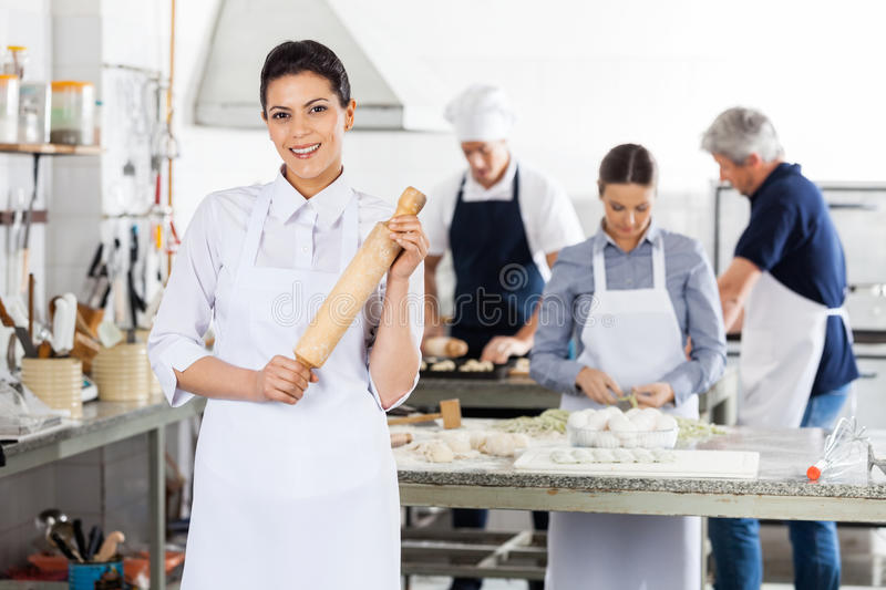 Weiblicher Chef Holding Rolling Pin While Colleagues stockbilder