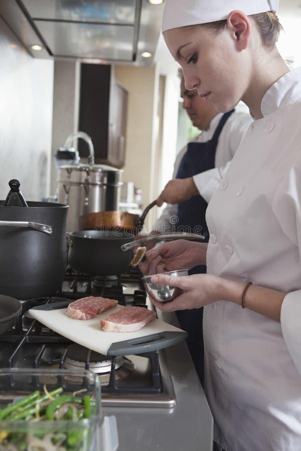 Weiblicher Chef Seasoning Raw Meat in der Küche stockbild