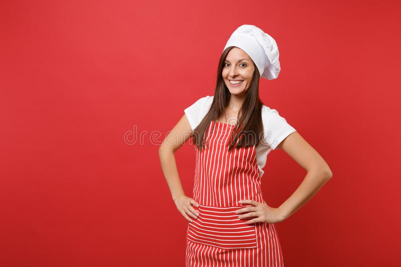 Weiblicher Chefkoch oder -bäcker der Hausfrau in gestreiftem Schutzblech, weißes T-Shirt, Toquechefhut lokalisiert auf rotem Wand lizenzfreies stockbild