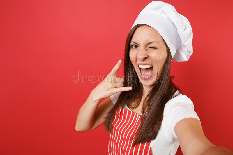 Weiblicher Chefkoch oder -bäcker der Hausfrau in gestreiftem Schutzblech, weißes T-Shirt, Toquechefhut lokalisiert auf rotem Wand stockfotos