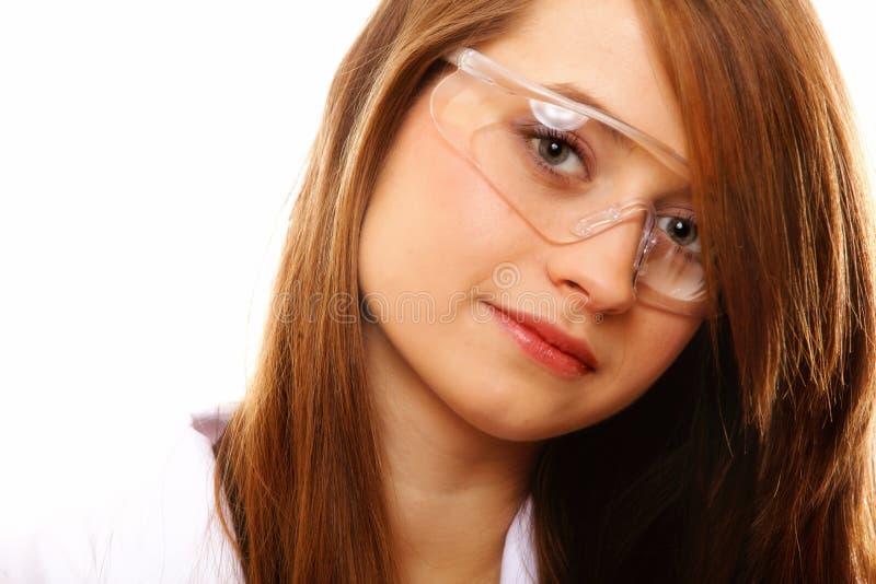 Weiblicher Chemiker des Porträts, der die Gläser lokalisiert verwendet lizenzfreie stockfotografie
