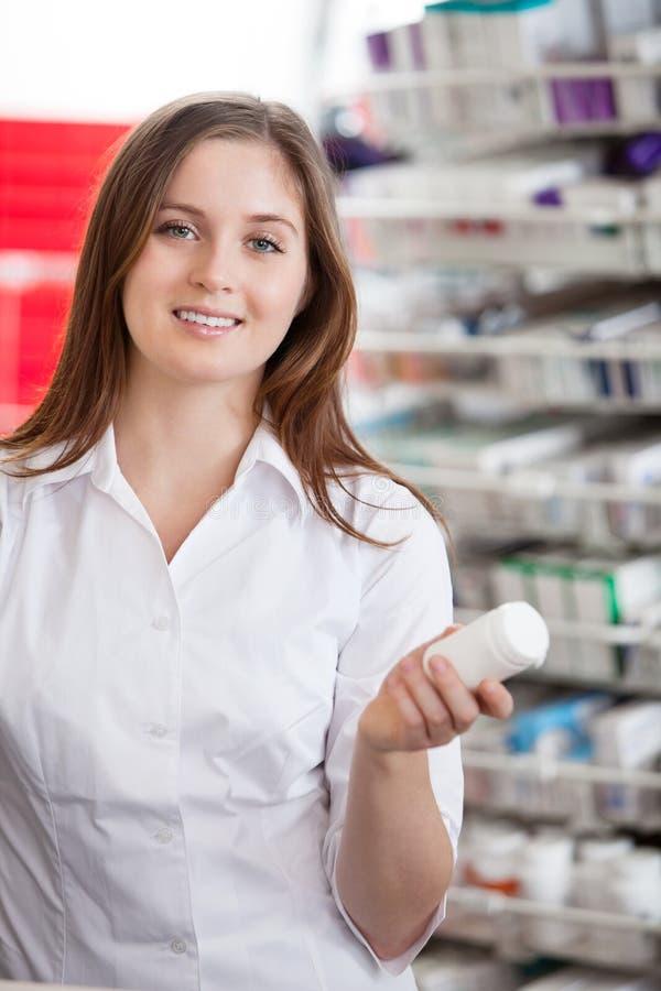 Weiblicher Chemiker-Holding-Medikation-Behälter stockfoto