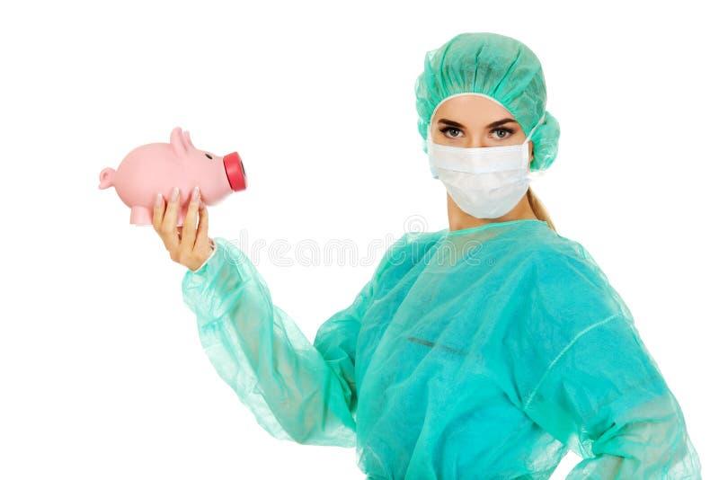 Weiblicher Chirurgdoktor, der Sparschwein hält lizenzfreies stockfoto