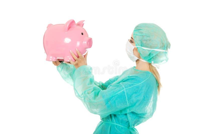 Weiblicher Chirurgdoktor, der Sparschwein hält lizenzfreie stockbilder