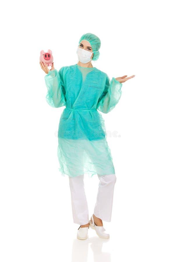 Weiblicher Chirurgdoktor, der Sparschwein hält lizenzfreies stockbild