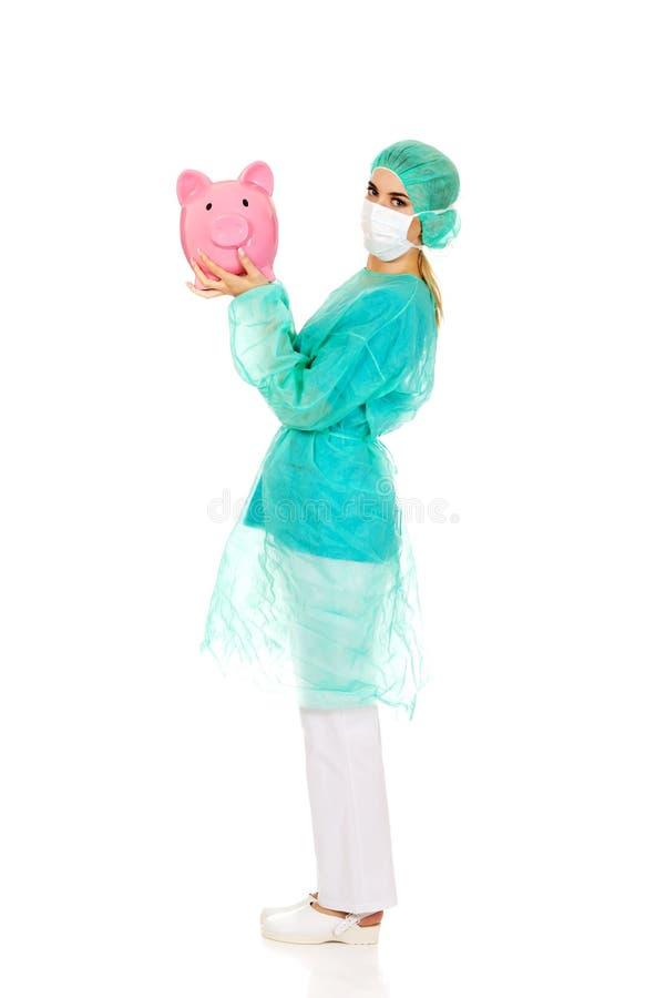Weiblicher Chirurgdoktor, der Sparschwein hält stockbilder