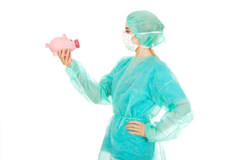Weiblicher Chirurgdoktor, der Sparschwein hält stockfotografie