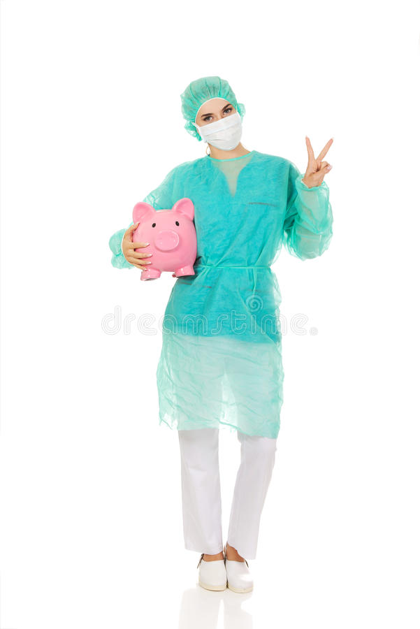 Weiblicher Chirurgdoktor mit Sparschwein zeigt Siegeszeichen lizenzfreie stockfotografie