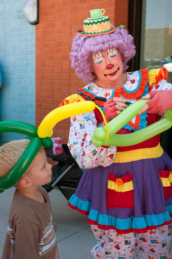 Weiblicher Clown stellt Ballon-Hut für Kind her stockfotografie