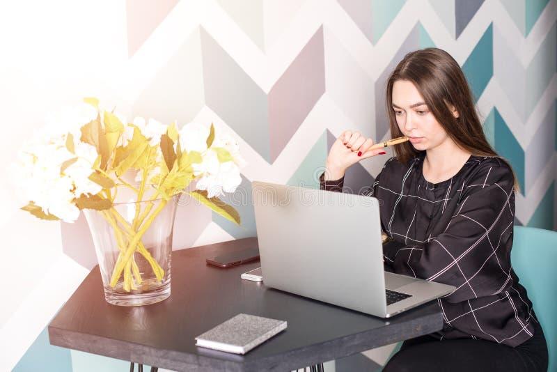 Weiblicher Designer, der an neue Ideen unter Verwendung des Netzbuches während des Restes in der Kaffeestube denkt Mädchenanmeldu stockbilder