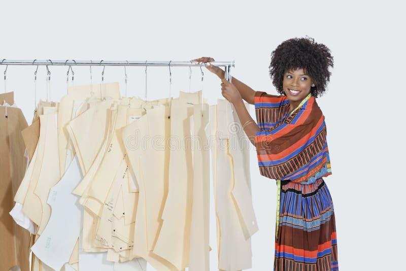 Weiblicher Designer des Afroamerikaners mit nähenden Mustern auf Kleiderständer über grauem Hintergrund stockfotografie