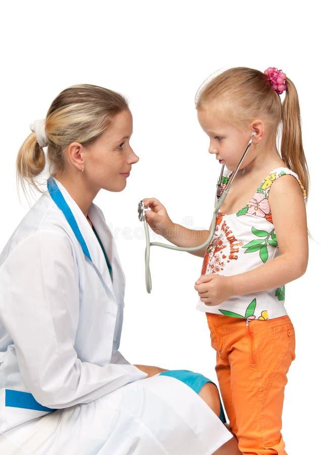 Weiblicher Doktor, der ein Kind überprüft stockfotografie