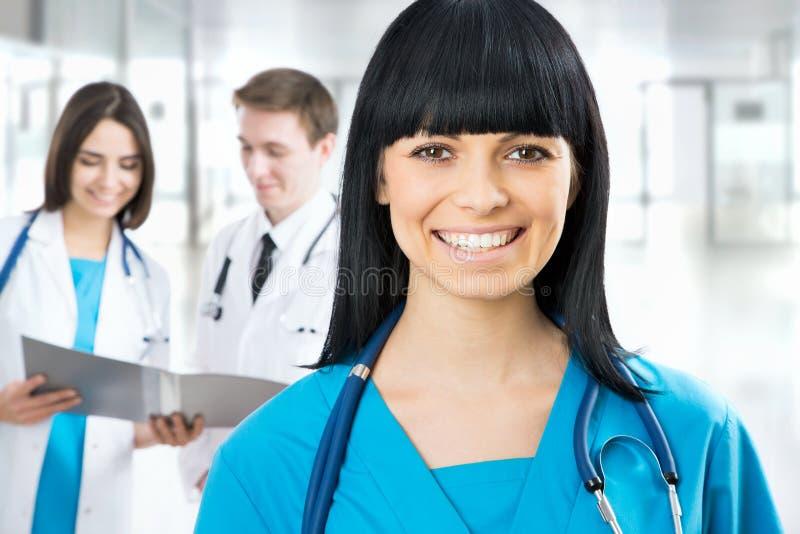 Weiblicher Doktor, der im frount seines Teams steht stockbild