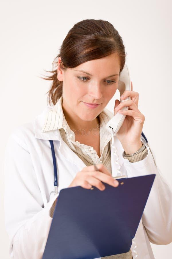 Weiblicher Doktor am Telefon mit medizinischer Datei lizenzfreie stockfotos