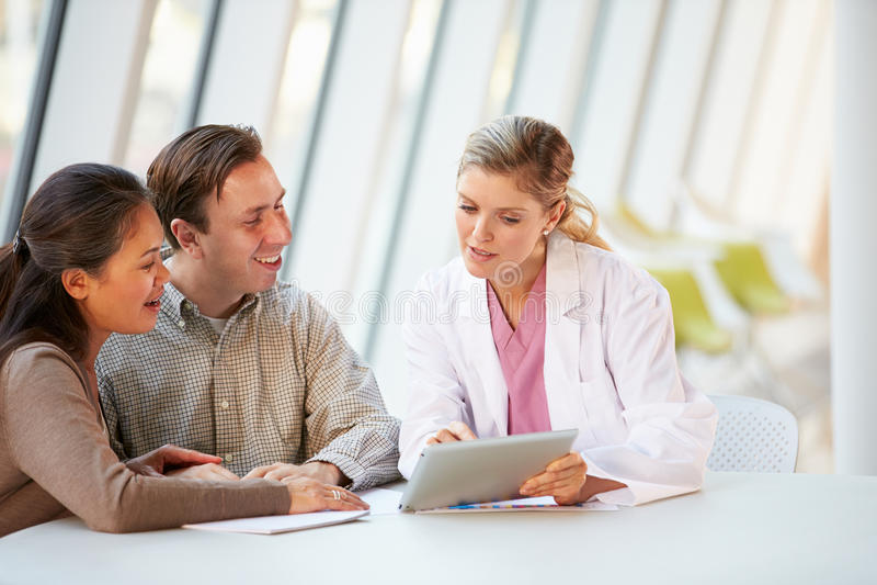 Weiblicher Doktor Using Digital Tablet Talking mit Patienten stockfotos