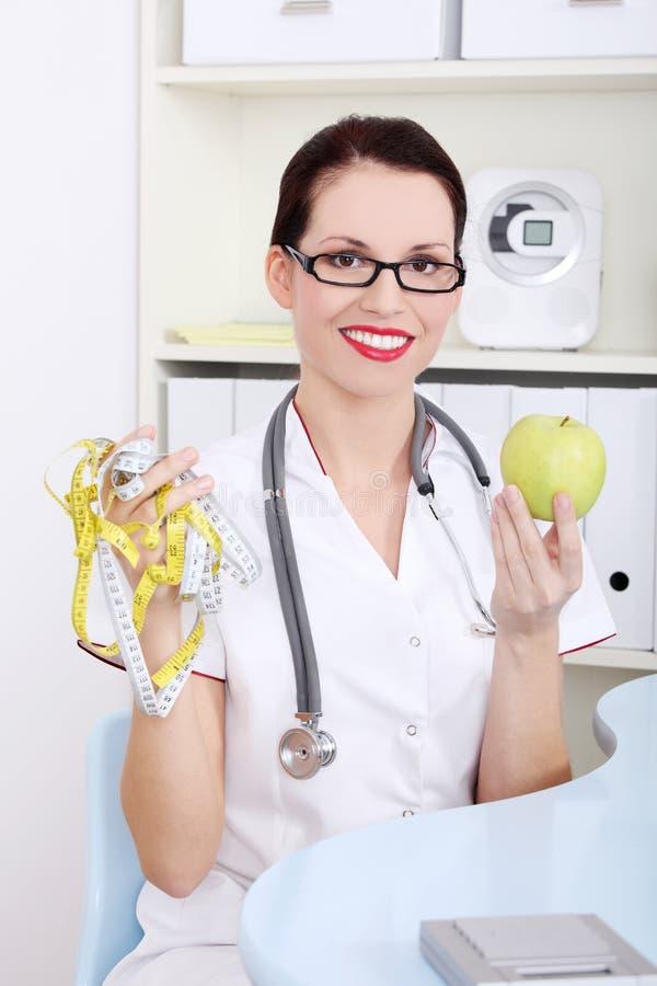 Weiblicher Doktorholdingapfel und messendes Band. lizenzfreie stockfotos