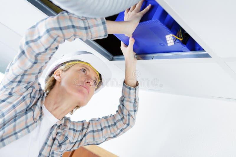 Weiblicher Elektriker, der elektrisches Ger?t in Decke installiert lizenzfreies stockfoto