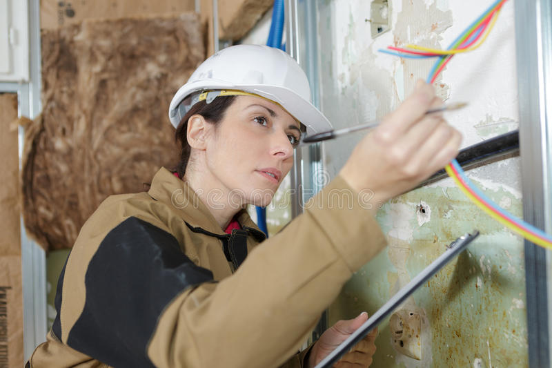 Weiblicher Elektriker, der Kabel kontrolliert stockfotografie