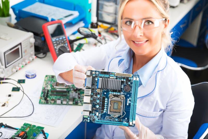 Weiblicher Elektronik-Ingenieur, der Computermotherboard in den Händen hält lizenzfreie stockbilder