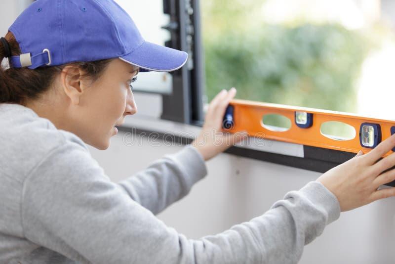 Weiblicher Erbauer, der Geistniveau auf Fensterrahmen verwendet stockfoto
