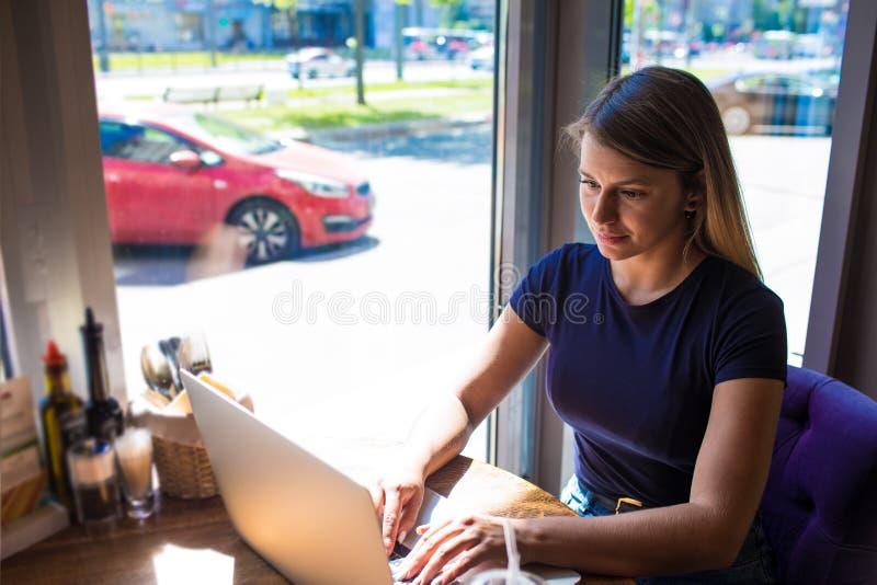 Weiblicher erfahrener Inserent, der fördernden Text auf Website über netbook schreibt lizenzfreie stockbilder