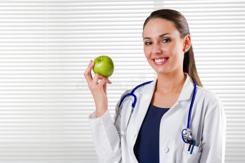Weiblicher Ernährungswissenschaftler, der einen grünen Apfel hält lizenzfreie stockfotografie