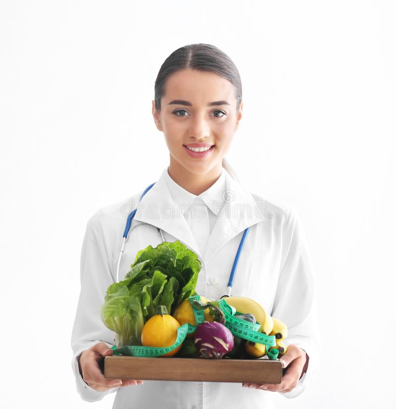 Weiblicher Ernährungswissenschaftler, der hölzernes Brett mit gesundem Gemüse und Früchten auf weißem Hintergrund hält lizenzfreie stockfotos