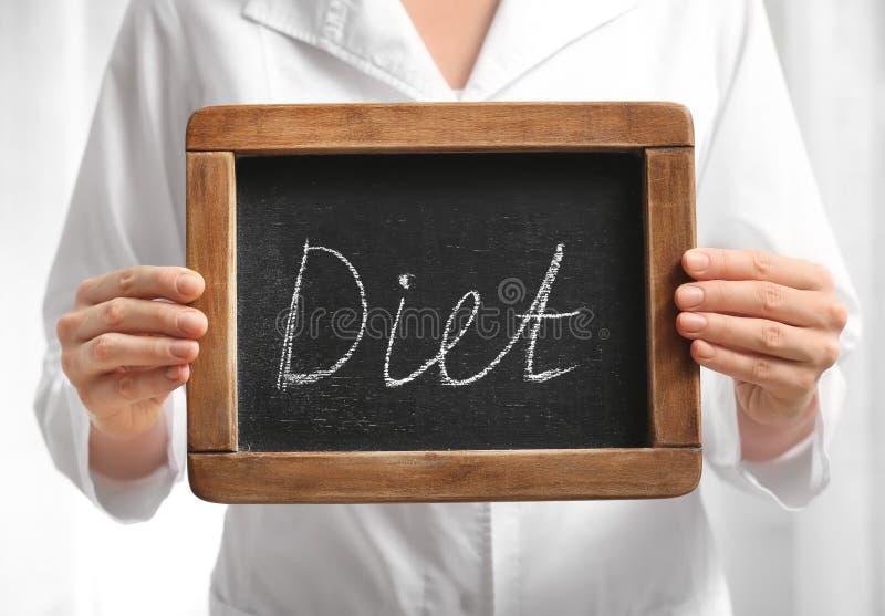Weiblicher Ernährungswissenschaftler, der kleine Tafel mit Wort DIÄT auf hellem Hintergrund, Nahaufnahme hält lizenzfreie stockfotografie