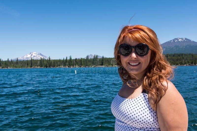 Weiblicher Erwachsener des recht roten Haares wirft durch Lava Lake entlang dem Cascade See-szenischen Seitenweg auf lizenzfreie stockfotografie