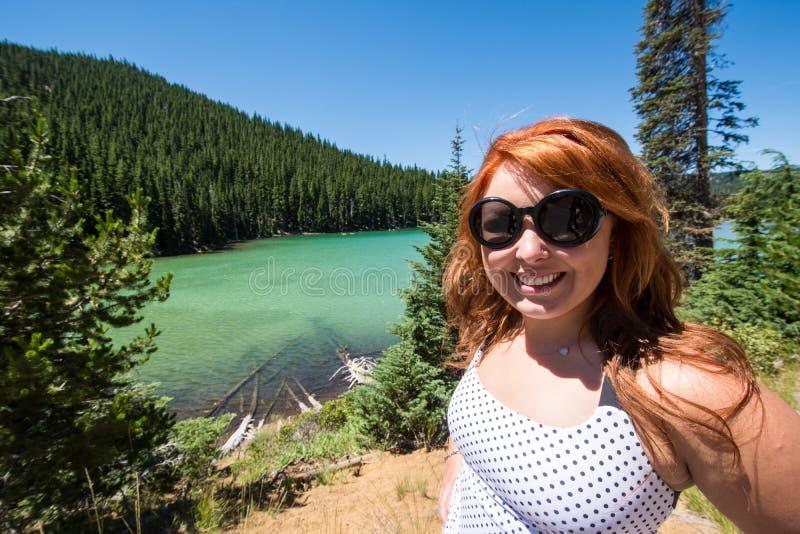 Weiblicher Erwachsener des recht roten Haares wirft durch Sparks See entlang dem Cascade See-szenischen Seitenweg auf stockfotos
