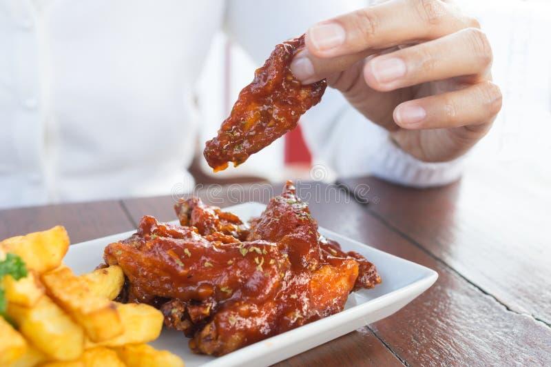 Weiblicher EssenHühnerflügel und Kartoffelchips stockfotos