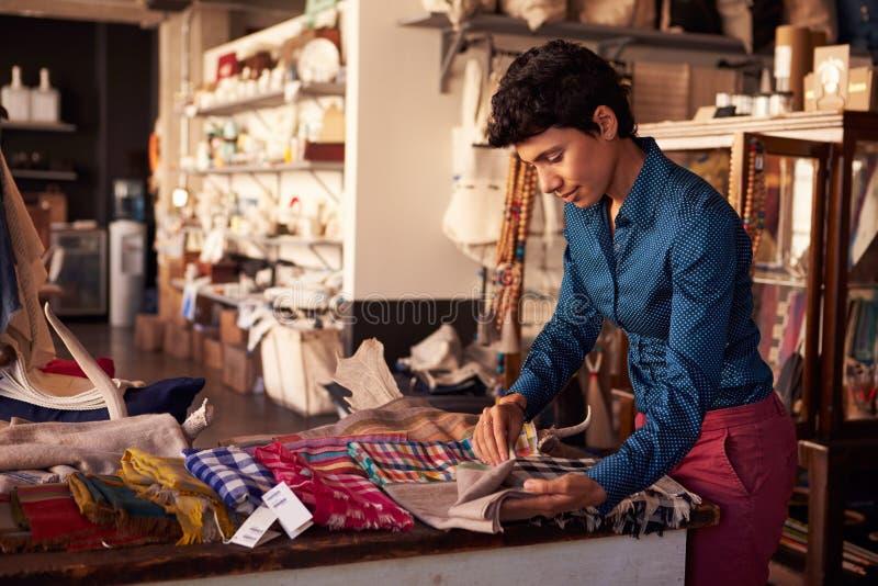 Weiblicher Fachverkäufer, der Gewebe in Homeware-Speicher vereinbart stockfotografie