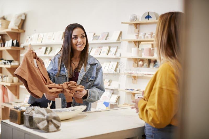 Weiblicher Fachverk?ufer in der unabh?ngigen Kleidung und Geschenkladen, der weiblichen Kunden dient stockbild