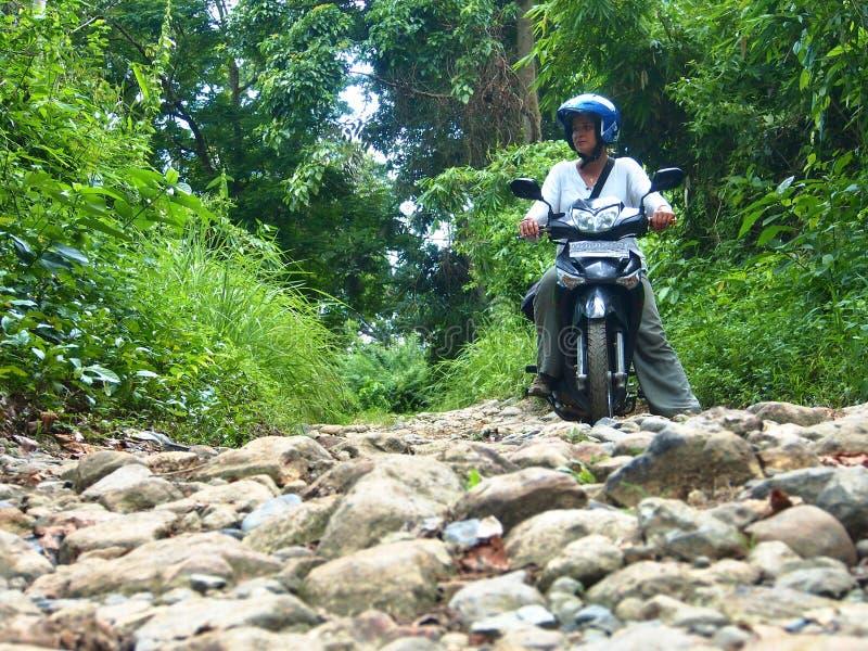 Weiblicher Fahrer With Motorbike On die steinige Straße stockfotos